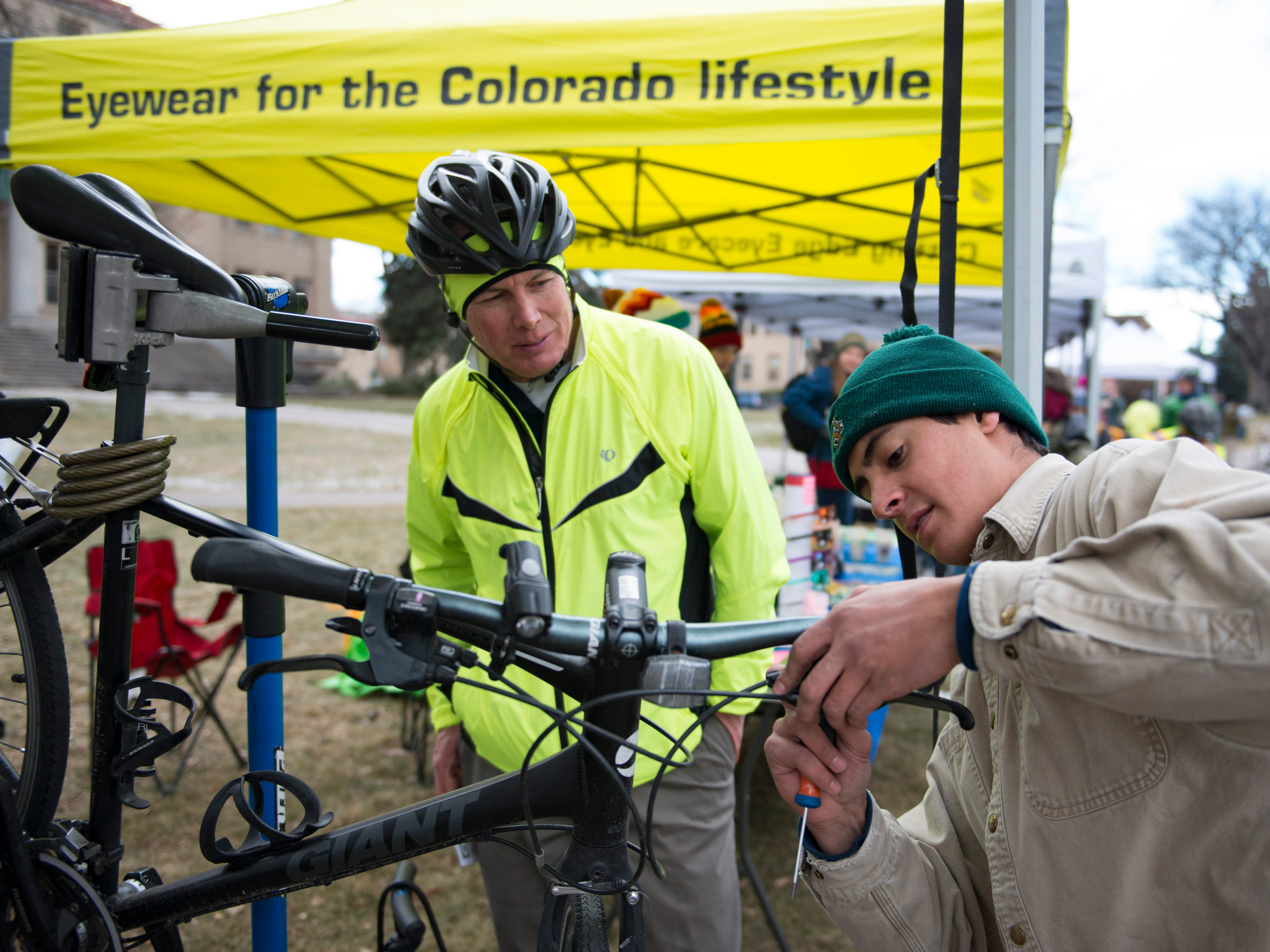 Shawn Baker gets a tune-up on his bicycle from Coleman Centola during Winter Bike to Work Day in the CSU Oval on Wednesday, December 12, 2018. Baker said he marks his calendar at work for every day he commutes by bicycle. Today was day 146 for the year.