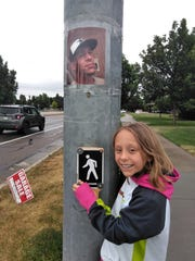 McKenzie, 9, poses with a photo of her father, 28-year-old Roger Talbot, taped to a pole at the intersection of Harmony and Timberline roads. McKenzie and her father were in a car crash at this intersection in March, and Roger died at the scene.
