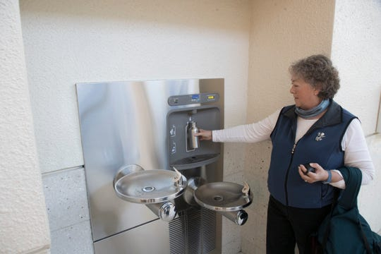 Southwest Florida International Airport traveler Robin Jenkins fills her water bottle on a new dispenser at the airport on Wednesday.  The airport has made some upgrades.