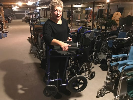 Colleen Crocker-MacMillin demonstrates the ease of use of a wheelchair donated to the Neighbor to Neighbor Volunteer Caregivers of Door County, Dec. 12, 2018.