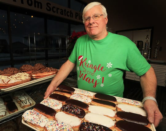 Owner Mike Vande Walle shows off a tray of baked goods at Uncle Mike's Bake Shoppe on Mason Street in Green Bay.