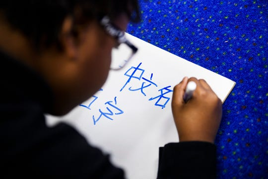 Samir Brockman writes in Mandarin during class at East Link Academy on Wednesday, Dec. 12, 2018.