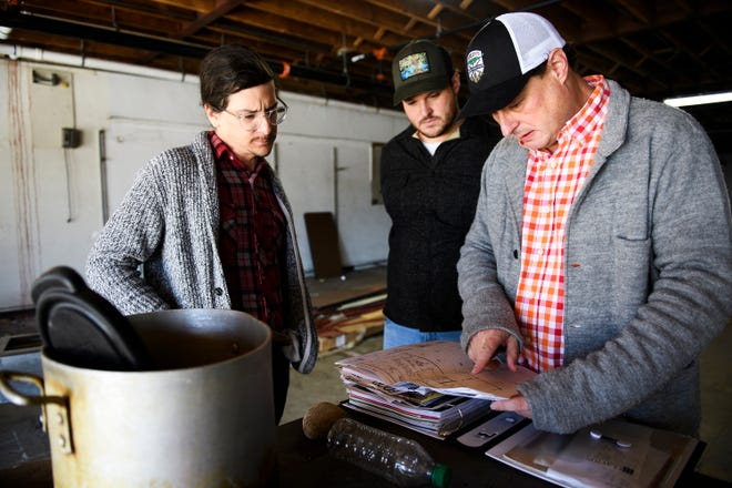 Josh Beeby, right, shows blueprints of his new restaurant, The Burrow, to general manager Robert Romanstine, left, and head chef Cory Massa, on Tuesday, Dec. 11, 2018.