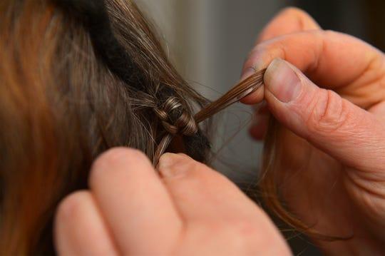 Jennifer Skinner of Sun River demonstrates how she ties in a custom dreadlocks hair extension that she makes from sheeps wool.