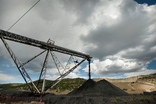 FILE - In this Sept. 26, 2011, file photo, raw coal from a coal mine pours off of a conveyer belt near Trinidad, Colo. Four states with climate change worries are asking a judge to stop the Trump administration from selling coal from public lands. Attorneys general from California, New Mexico, New York and Washington are due in a U.S. courtroom in Montana Thursday, Dec. 13, 2018, to argue the sales put the climate at risk and shortchange taxpayers. (Mark Reis/The Gazette via AP)