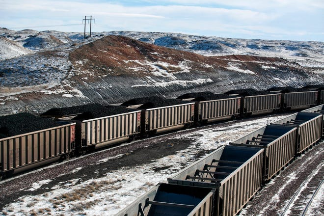 FILE - In this Jan. 9, 2014, file photo, rail cars are filled with coal and sprayed with a topper agent to suppress dust at Cloud Peak Energy's Antelope Mine north of Douglas, Wyo. Four states with climate change worries are asking a judge to stop the Trump administration from selling coal from public lands. Attorneys general from California, New Mexico, New York and Washington are due in a U.S. courtroom in Montana on Thursday, Dec. 13, 2018, to argue the sales put the climate at risk and shortchange taxpayers. (Ryan Dorgan/The Casper Star-Tribune via AP, File)