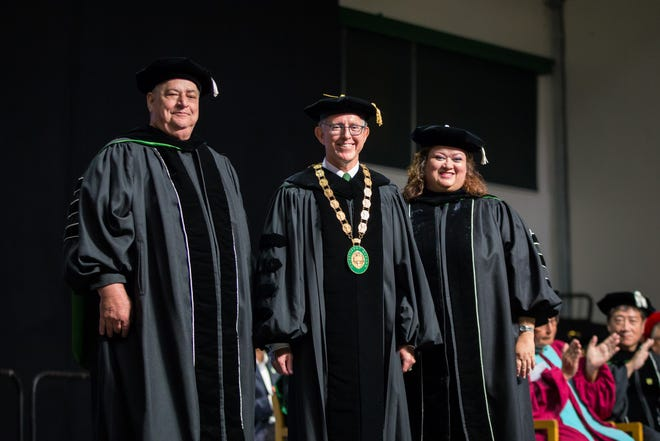 """Incoming University of Guam Board of Regents Chairperson Christopher K. Felix, left, and outgoing Chairperson Elizabeth """"Betty"""" Gayle present President Thomas W. Krise with the Presidential Medallion of Office at his Nov. 16 investiture ceremony."""