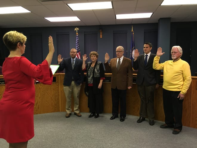 Circuit Judge Karen L. Wilson swears in city commissioners Brad Staton, Patti Bugg, Austin Vowels and XR Royster, along with Mayor Steve Austin, Tuesday evening.