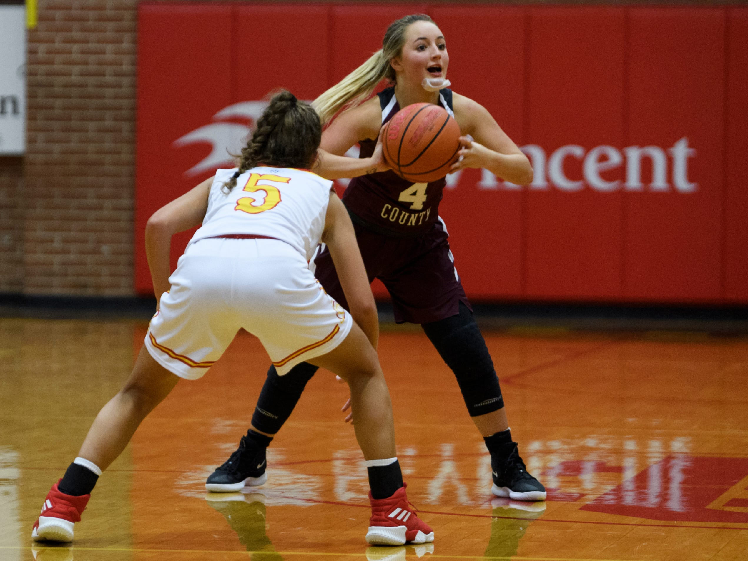 Henderson County's Savannah Lacer (4) looks to make a pass as Mater Dei's Alaina Spahn (5) guards her at Mater Dei High School in Evansville, Tuesday, Dec. 11, 2018. The Lady Colonels defeated the Wildcats 53-40.