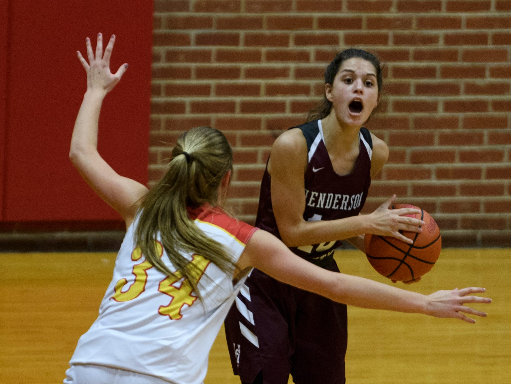 Henderson County's Katie Rideout (10) yells for her teammates to get into an open passing position as Mater Dei's Kelsey Carr (34) guards her during the second quarter at Mater Dei High school in Evansville, Tuesday, Dec. 11, 2018. The Lady Colonels defeated the Wildcats 53-40.