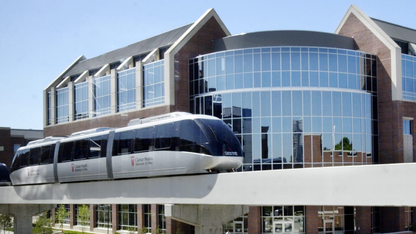 The people mover goes above Walnut Street. In the background is an IUPUI research building at 950 Walnut. On the right is a Wishard parking garage.