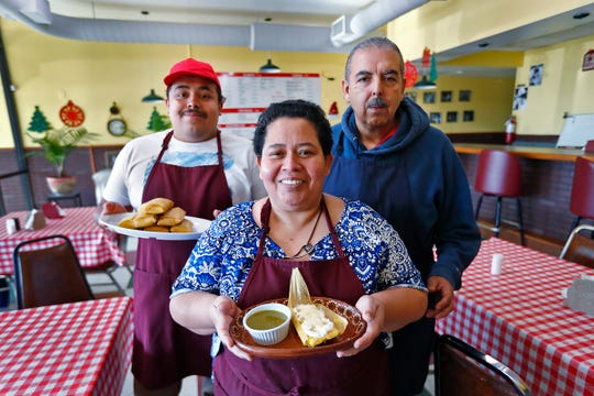 Maria Vasquez, center, standing with her son, Adrian Vasquez, left, and her husband, Juan Vasquez, right, shows tamales they made, at Pico de Gallo restaurant, Tuesday, Dec. 11, 2018.  The family is making the traditional food for the Carmel Farmer's Market.