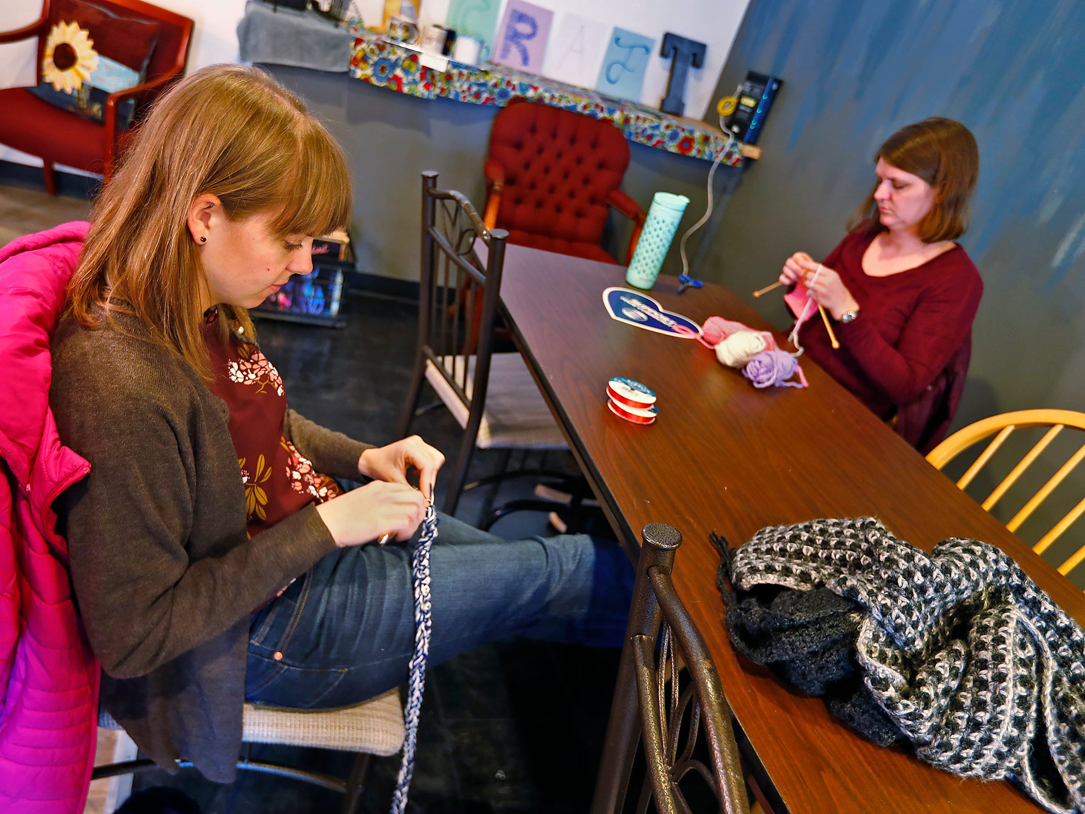 Jenna Page, left, and Kelly Carter knit hats and scarves for the homeless on Give Back Day at ReCraft, Tuesday, Dec. 11, 2018.  ReCraft was born out of Bethany Daugherty's love of crafting and her interest in environmental activism.  At the secondhand craft and hobby store, Daugherty also teaches workshops.  Sustainability and environmentalism are the focus of the store.
