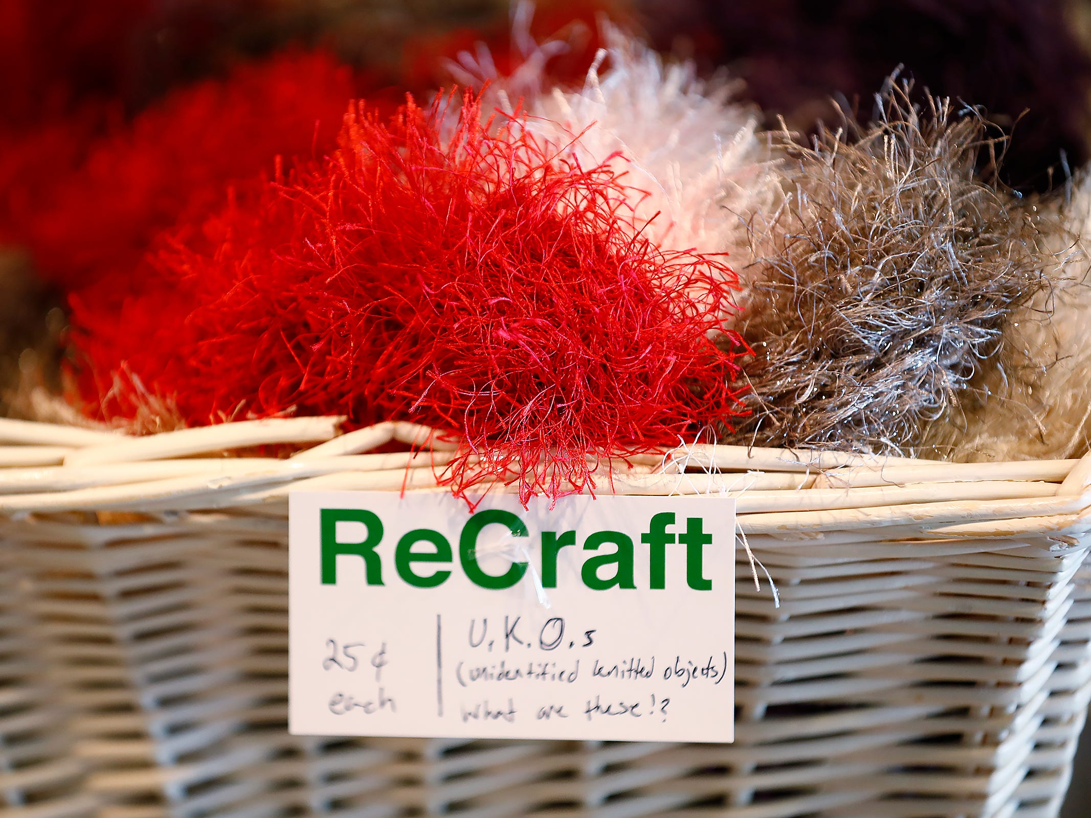 A basket of unknown knitted objects are seen for sale at ReCraft, Tuesday, Dec. 11, 2018.  Many of the store's items are donated or ready for re-use. ReCraft was born out of Bethany Daugherty's love of crafting and her interest in environmental activism.  At the secondhand craft and hobby store, Daugherty also teaches workshops.  Sustainability and environmentalism are the focus of the store.