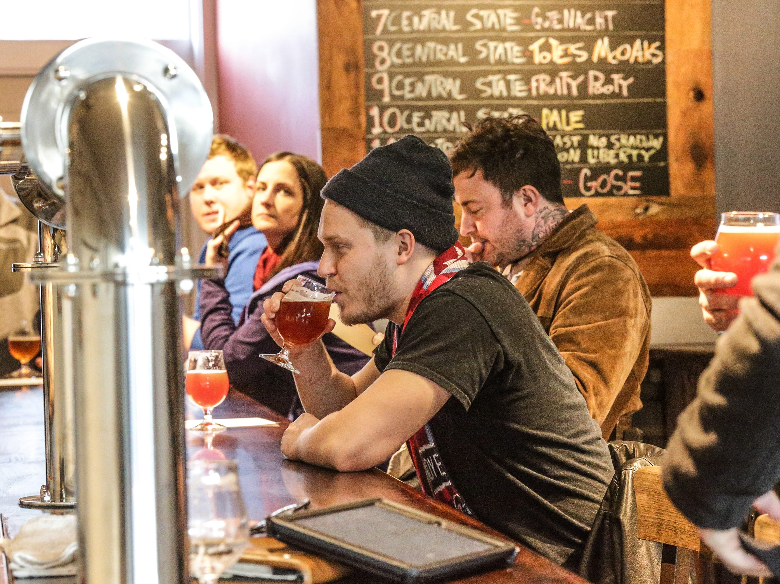 Milk Tooth's Nate Atkins, center, and Jonathan Brooks, center right, sample brews during Central State Brewery's  Koelschip Tap Room's soft opening.
