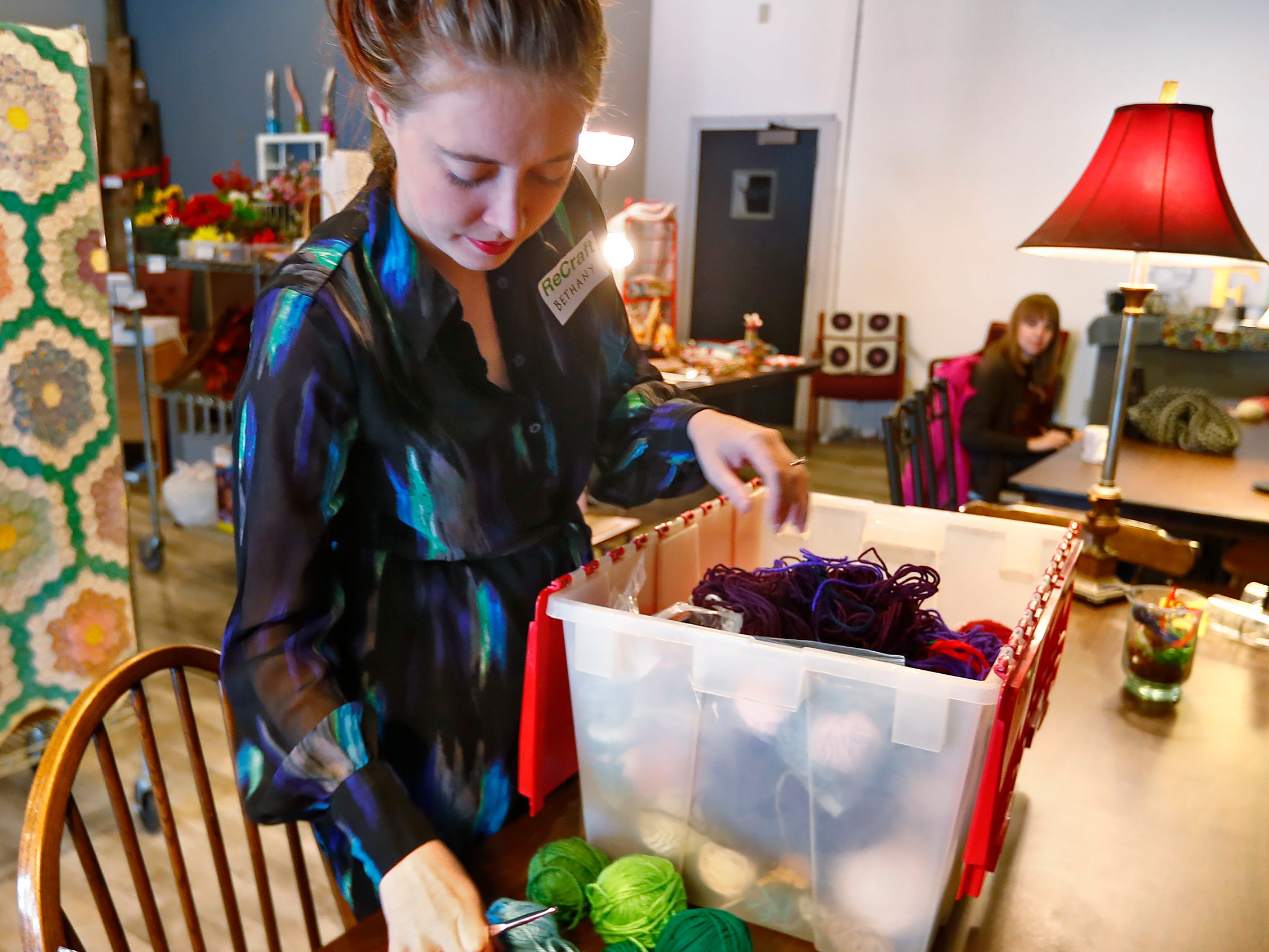Bethany Daugherty gets ready to crochet at ReCraft, Tuesday, Dec. 11, 2018.  ReCraft was born out of Daugherty's love of crafting and her interest in environmental activism.  At the secondhand craft and hobby store, Daugherty also teaches workshops.  Sustainability and environmentalism are the focus of the store.  This day at ReCraft is Giving Back Day.  Customers are welcomed to come in to knit or crochet hats and scarves for the homeless.