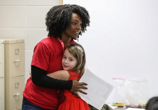 """Volunteer Gabrielle Flowers Rader receives a hug from third-grader Anna during a Girls, Inc. of Greater Indianapolis session, at Mary Castle Elementary in Indianapolis, Tuesday, Dec. 11, 2018. Girls Inc. of Greater Indianapolis is the local branch of a nonprofit that aims to make girls """"strong, smart, andÊbold,"""" offering eight, free six-week courses to 85 Indiana partner schools."""