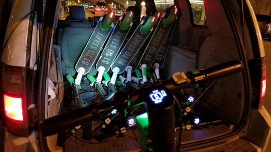 Lime scooters are stacked in a van used by volunteers with We Are Family Indy Homeless Outreach on Dec. 7, 2018. Volunteers plug in the scooters in the van so they charge as they drive around looking for more.