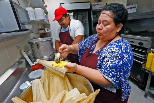 Maria Vasquez fills tamales she is making as her son Adrian Vasquez, left, helps with the process, at Pico de Gallo restaurant, Tuesday, Dec. 11, 2018.  The family is making the traditional food for the Carmel Farmer's Market.