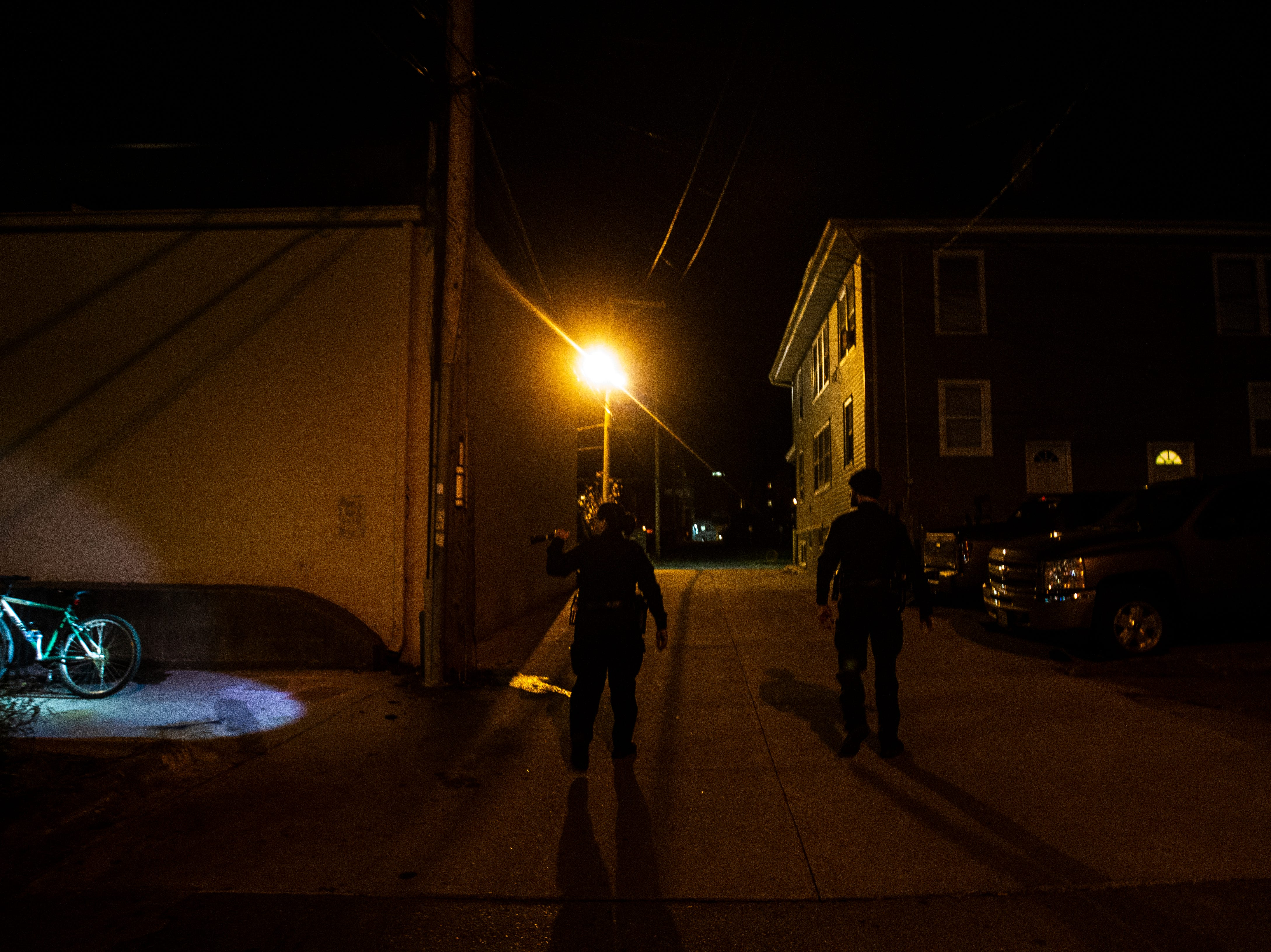 Iowa City Police Officers check an alleyway on Wednesday, Oct. 31, 2018, at  in Iowa City.