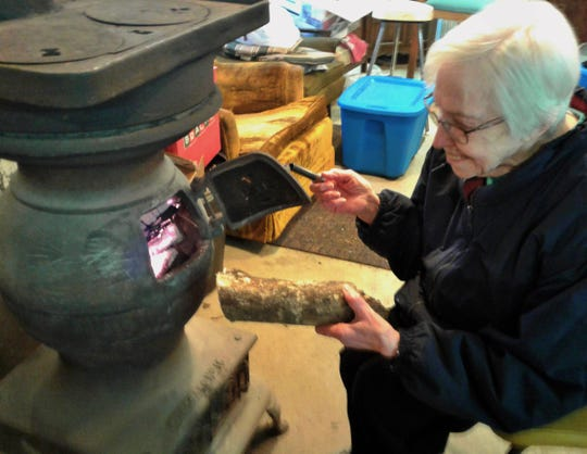 Margaret Handley could be seen Saturday morning loading a log into the unique wood-burning stove which heats the working office at Handley's Holiday Hillside Christmas tree farm east of Solon.  She says the stove once warmed railroad workers in a caboose.