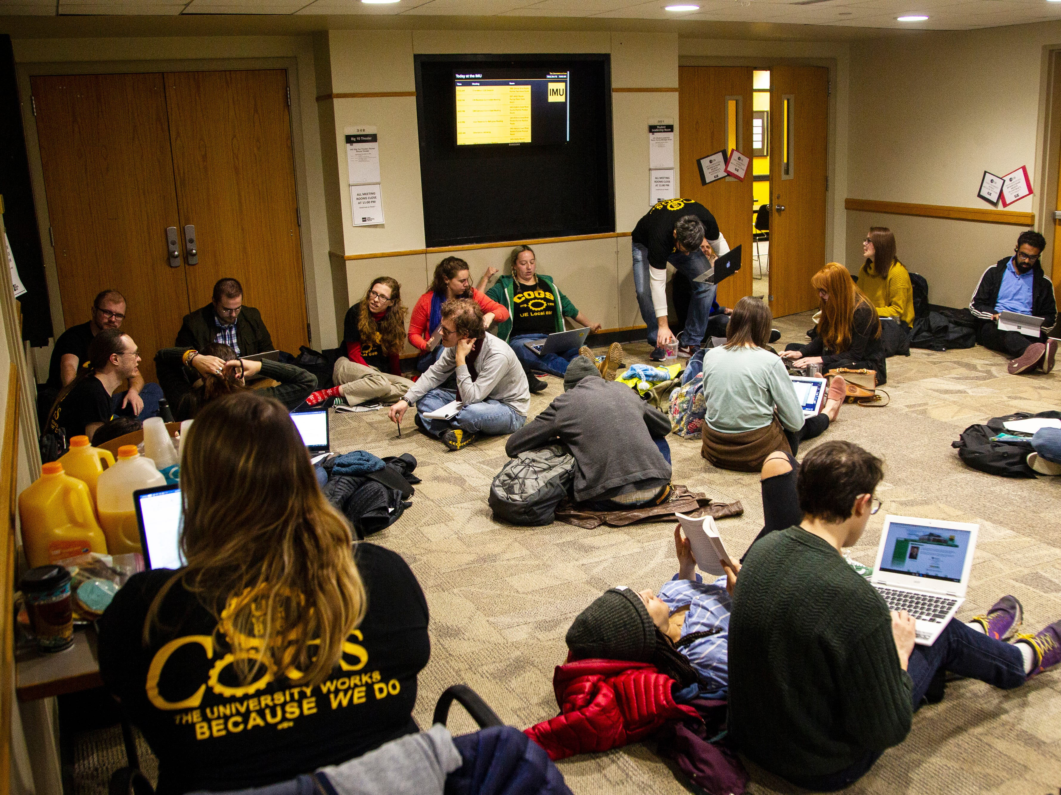 Campaign to Organize Graduate Student members stage a sit-in before a contract proposal from the Iowa Board of Regents on Wednesday, Dec. 12, 2018, at the Iowa Memorial Union in Iowa City. The graduate students sat in the hallway grading work for two hours before meeting the Regents' representatives.