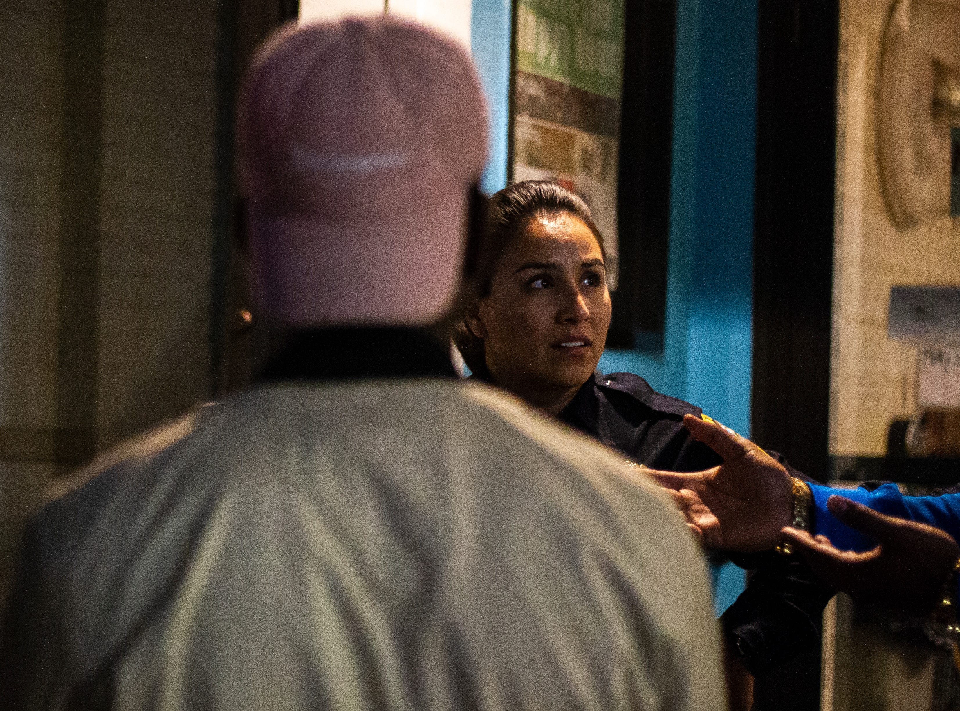 Iowa City Police Patrol Officer Pamela Romero talks with patrons outside a bar on Thursday morning, Nov. 1, 2018, in downtown Iowa City.