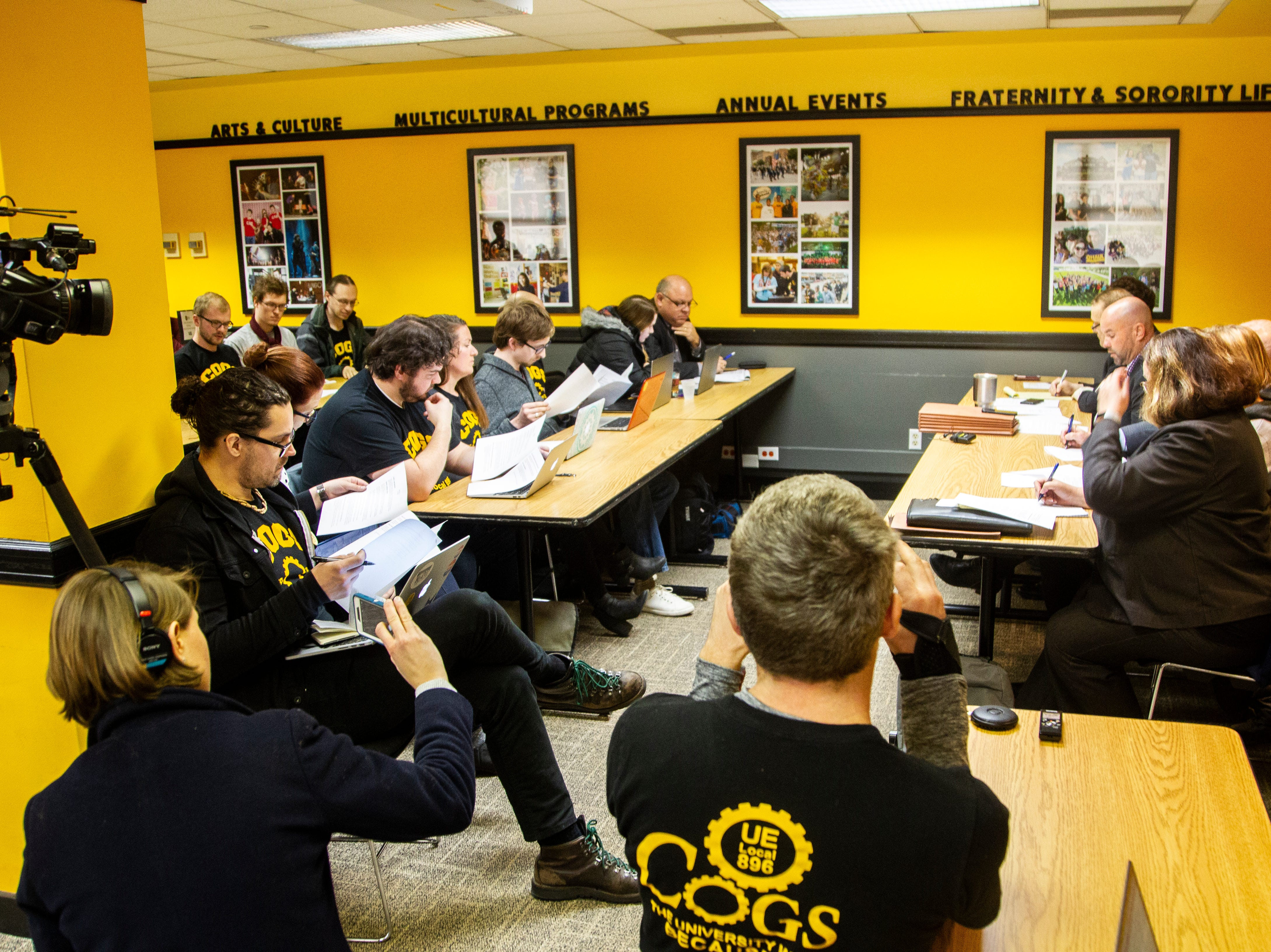 Campaign to Organize Graduate Students members look through a one page document from Regents lawyer Mike Galloway during a contract proposal from the Iowa Board of Regents on Wednesday, Dec. 12, 2018, at the Iowa Memorial Union in Iowa City.