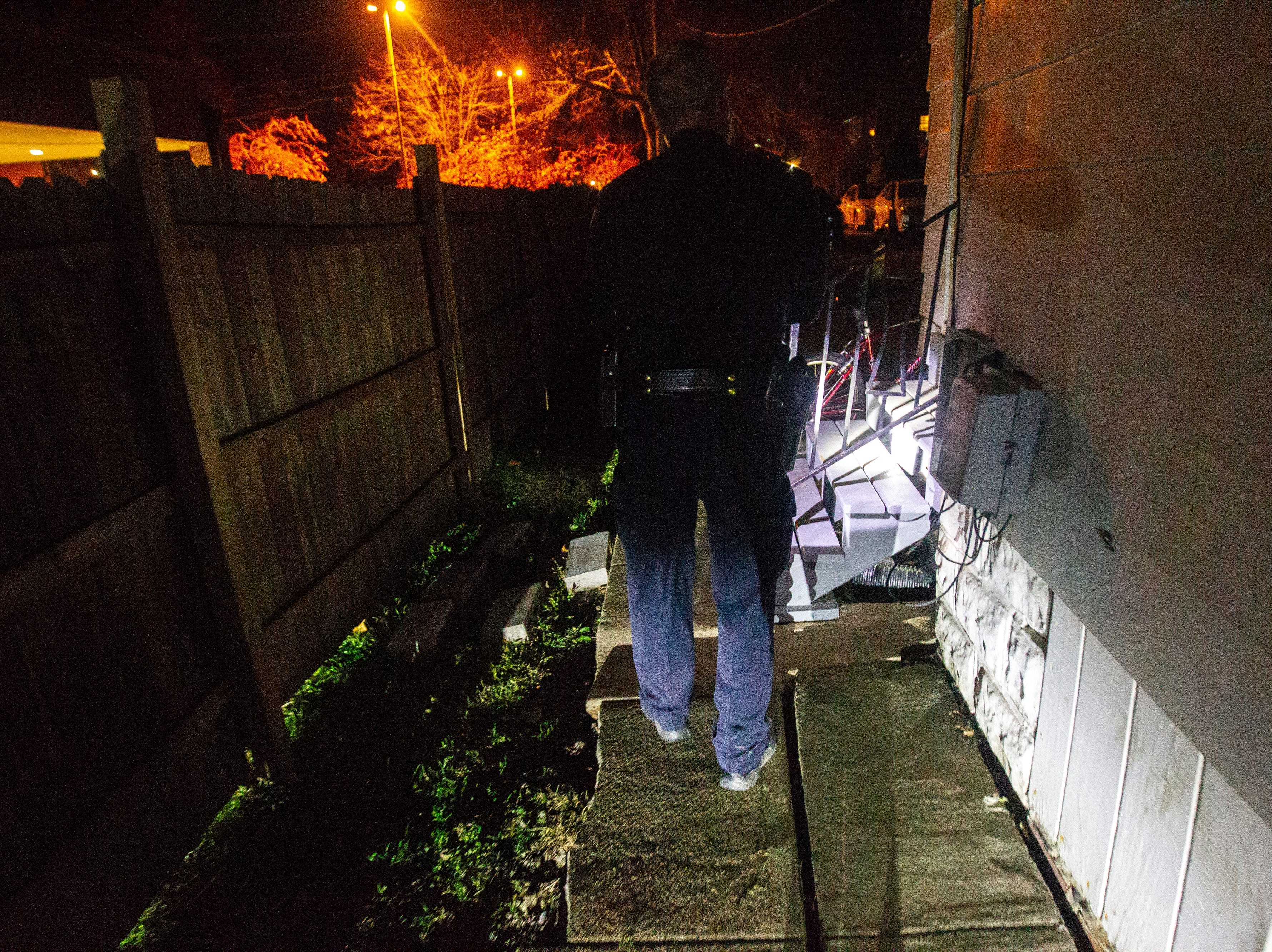 Iowa City Police Officer Doug Roling checks the back steps of a house party on Wednesday, Oct. 31, 2018, in the north side neighborhood in Iowa City.
