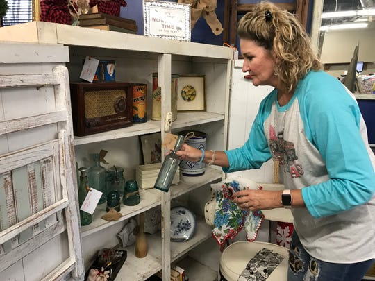 Donna McGarrh of Madison arranges items at Antique Aly in Ridgeland.