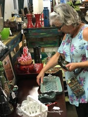 Cindy Powell of Madison adds price tags to items in her both at Antique Aly in Ridgeland.