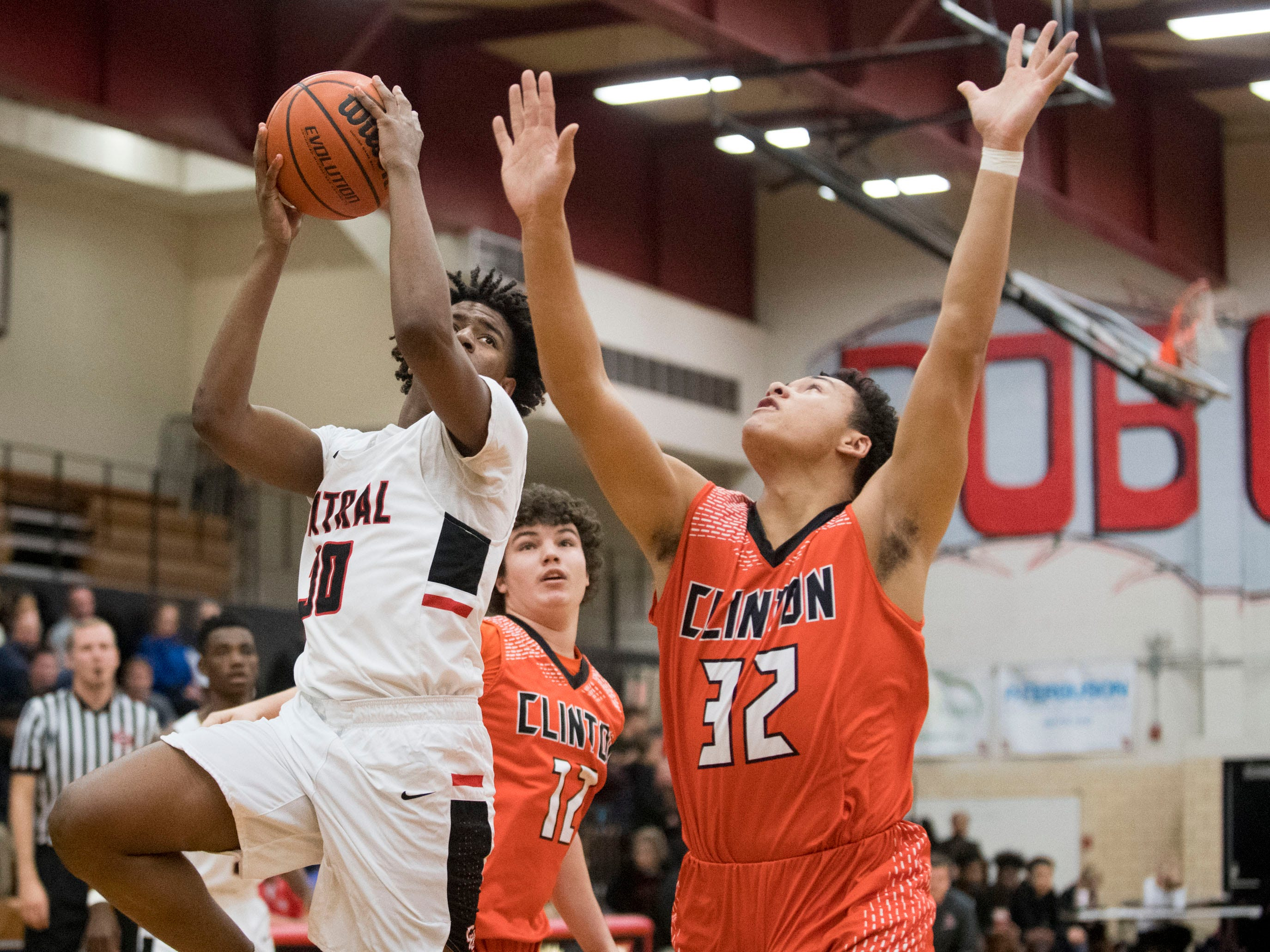 Central's Ahmad Belton Jr. (30) looks for the shot while defended by Clinton's DeMarcus McKamey (32) on Tuesday, December 11, 2018.