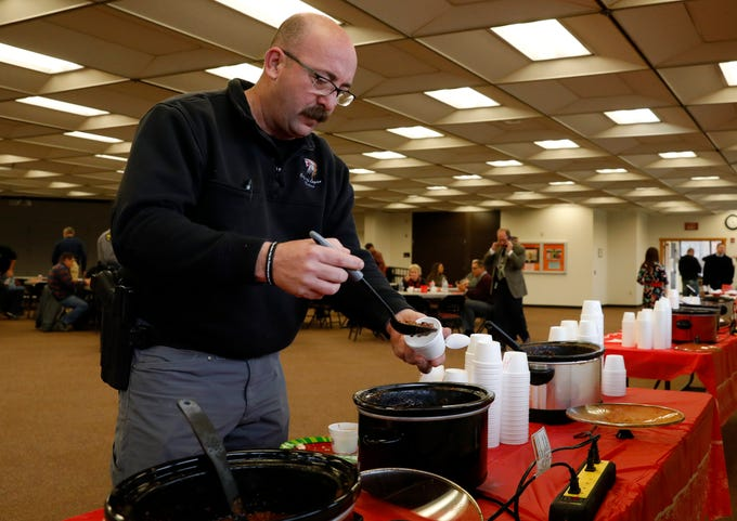 Logan Police Capt. Ryan Gabriel ladles chili into a cup as he prepares to judge the Fairfield-Hocking-Athens Major Crimes Unit's annual chili cook-off in Lancaster.