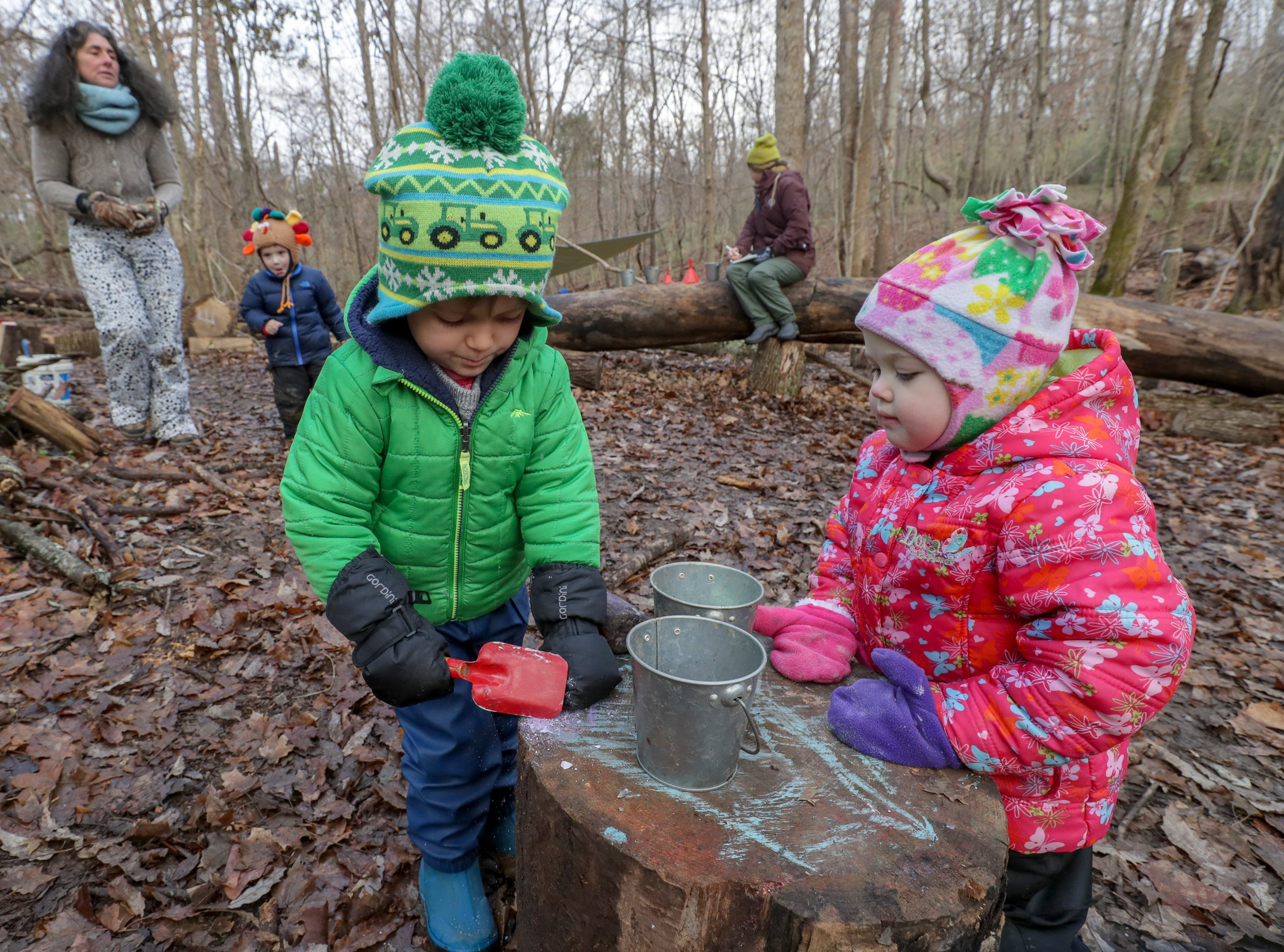 Ferris Devlin and Hannah Rose O'Connell work to make a concoction from leaves, twigs, mud, stream water and chalk at Thrive Forest School at Creasey Mahan Nature Preserve.November 19, 2018