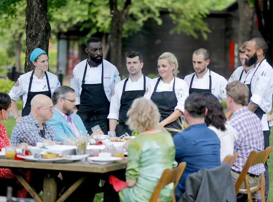 "(Left to right) Chefs Natalie Maronski, Eric Adjepong, Eddie Konrad, Kelsey Barnard, Pablo Lamon, Brandon Rosen and Justin Sutherland present their dishes during a challenge on episode 2 of ""Top Chef"" season 16."