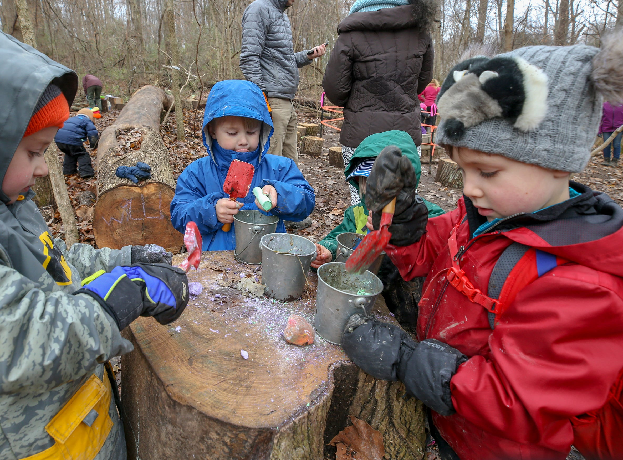 Students at Thrive Forest School, including Quinn Mahoney, left, and Will Clark, right, work to create a concoction using leaves, twigs, mud, stream water and chalk at Creasey Mahan Nature Preserve.November 19, 2018