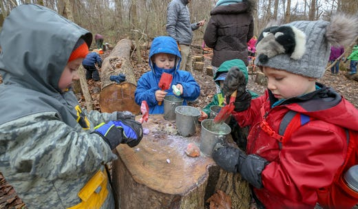 Students at Thrive Forest School, including Quinn Mahoney, left, and Will Clark, right, work to create a concoction using leaves, twigs, mud, stream water and chalk at Creasey Mahan Nature Preserve. November 19, 2018