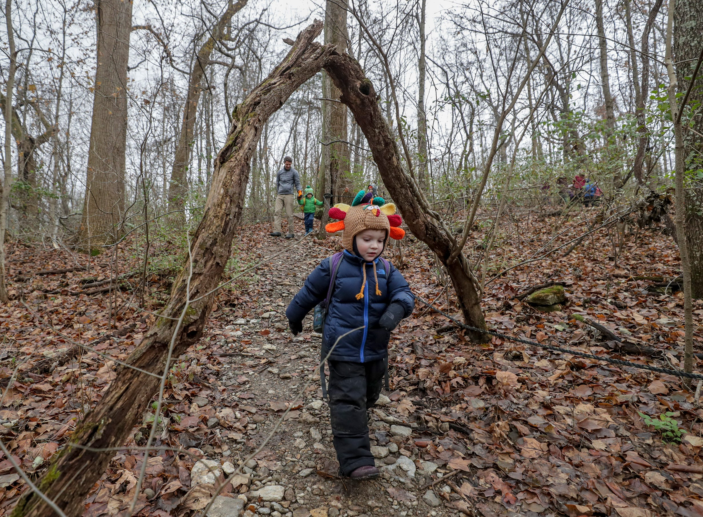 Lincoln Oakes walks under a tree limb that forms a natural arch for the entrance for Thrive Forest School.November 19, 2018