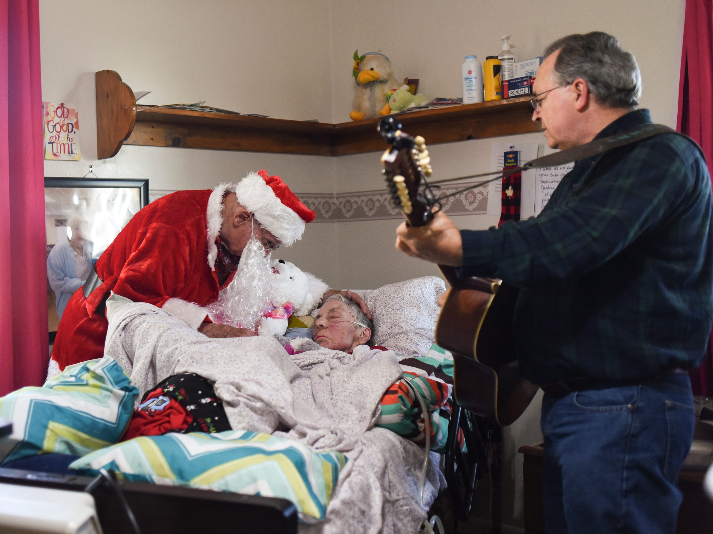 "Don West, 90, of Eaton Rapids, leans in to kiss his wife Jackie goodnight, Saturday, Dec. 8, 2018, at Golden Days II Adult Foster Care in Charlotte, after a Christmas party for residents and staff.  Don hired musician Dennis Michaels, right, to play music.  ""We both loved to listen to music and dance,"" he said.  Don brought gifts for residents and staff, with the tags reading ""from Jackie."""