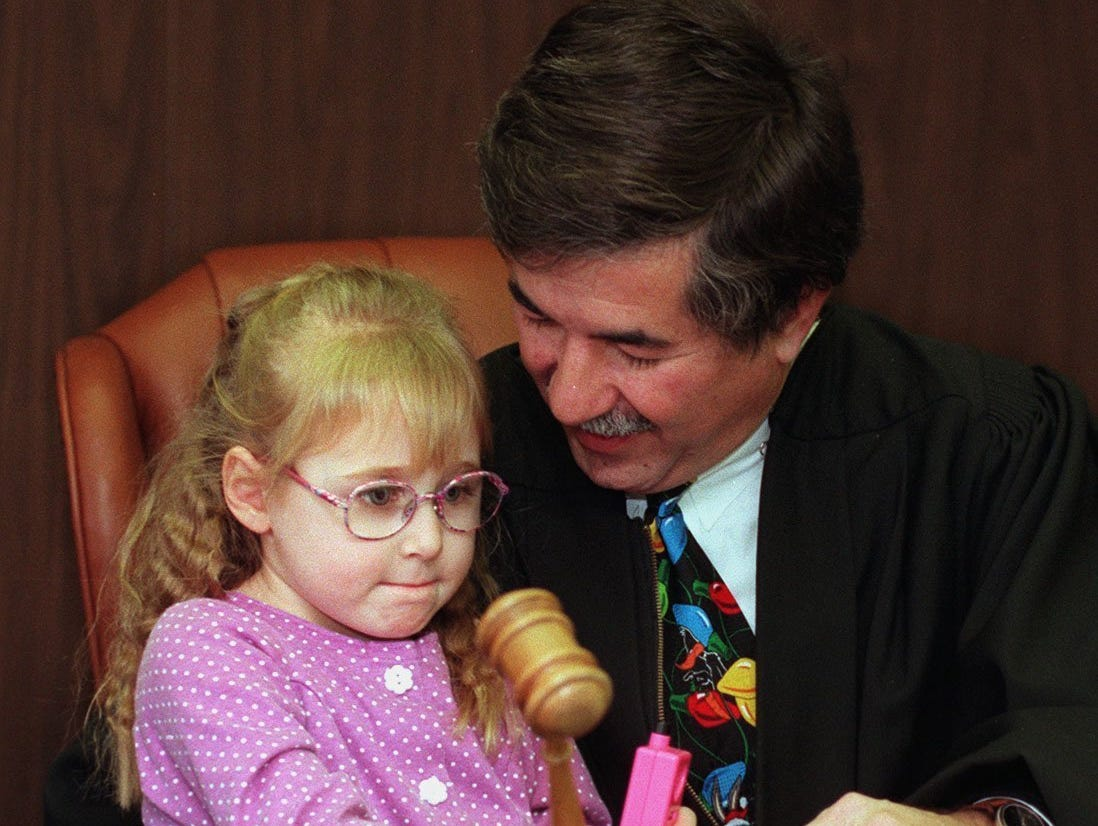 Jackie Lynn, 4, sounds the gavel of Judge R. George Economy, making her adoption to Ron Daman official Monday morning, Dec. 23, 1996.