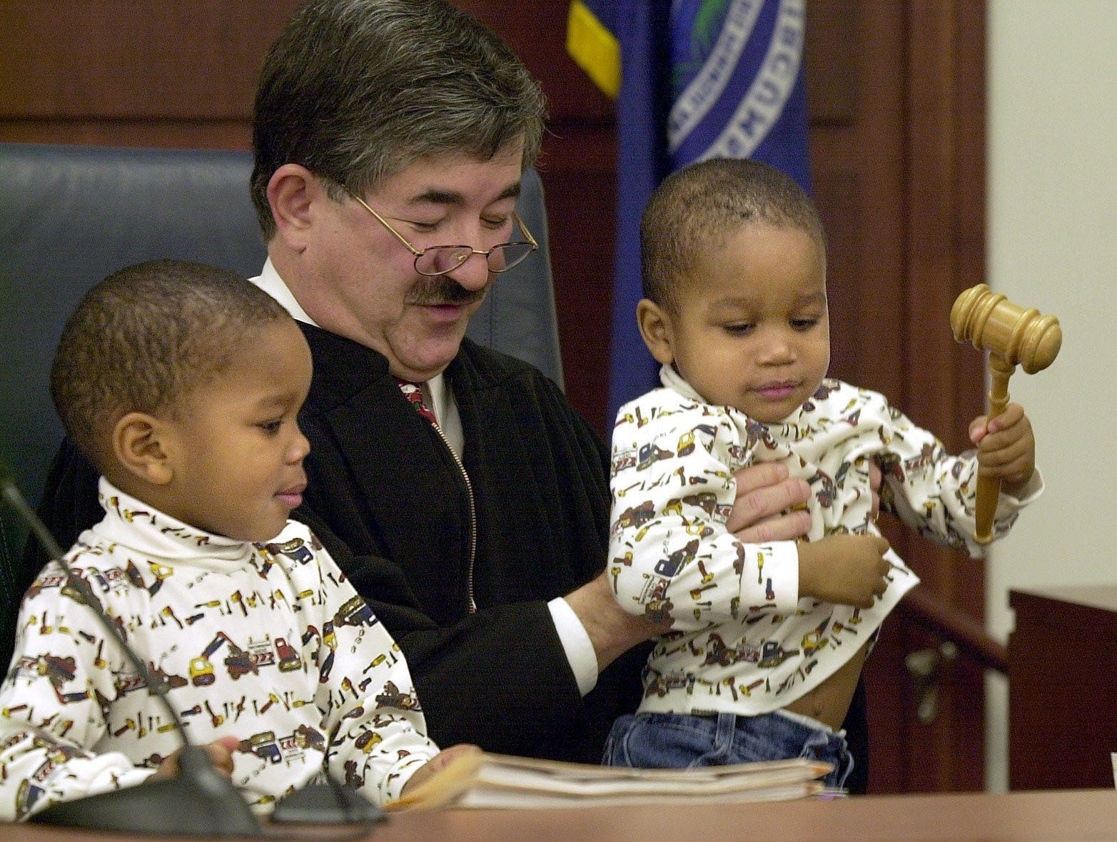 Brothers George Duane Curtis, 3, left, and Tyre Lee Curtis, 2, right, sit on Ingham County Family Court Judge George Economy's lap and bang the gavel  Dec. 19, 2001 as Economy finalizes their adoption by mom and dad Darlene and Duane Curtis in his traditional Christmas season adoption proceedings.