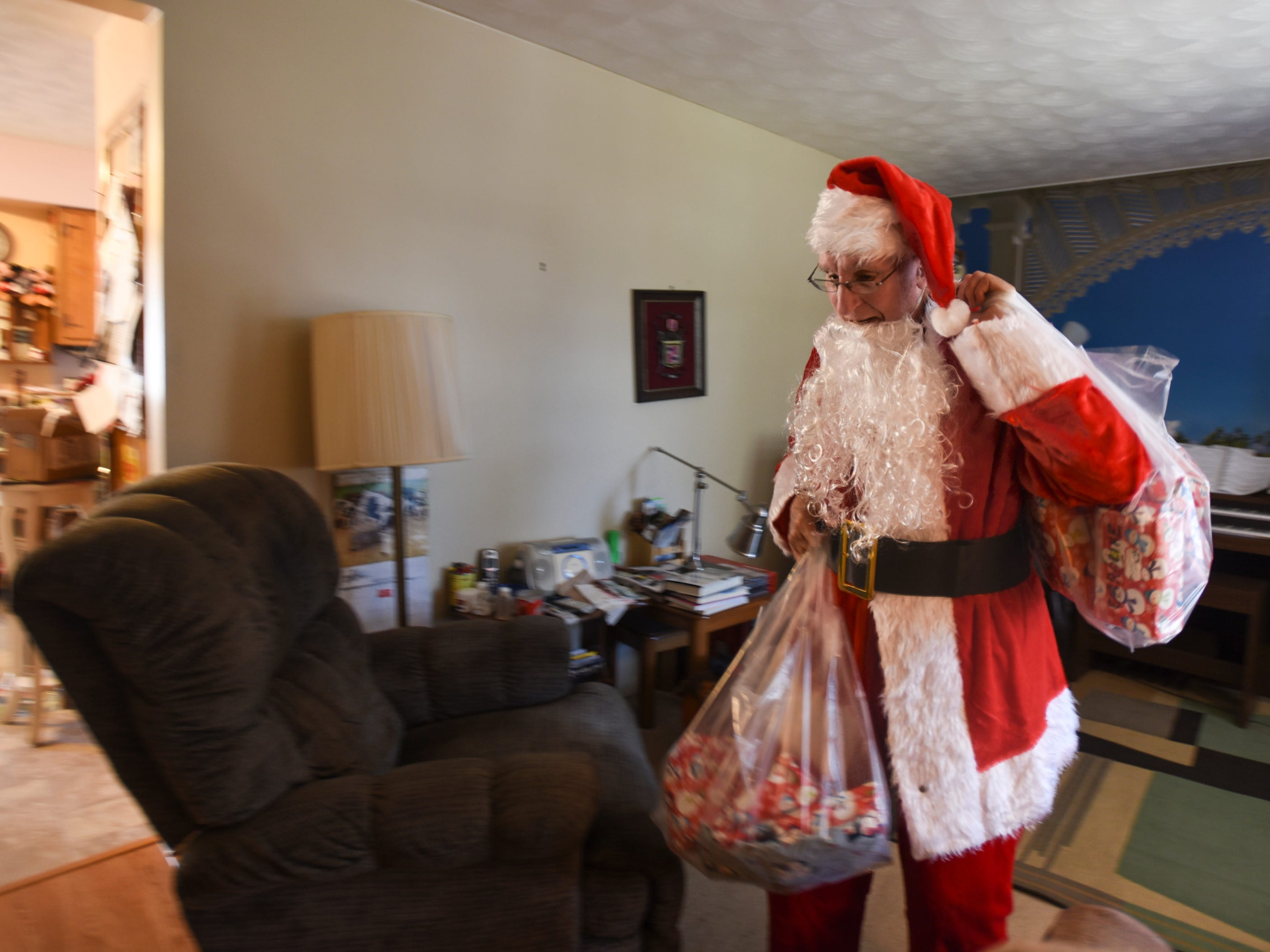 Dressed as Santa, Don West, 90, of Eaton Rapids, grabs two satchels of gifts he wrapped for workers and residents at Golden Days II Adult Foster Care in Charlotte, Michigan, Saturday, Dec. 8, 2018. He's heading to Charlotte from his home in Eaton Rapids, where he'll deliver the presents, and sing and dance for his wife Jackie, who's been in a nursing home since her stroke in June of 2017.