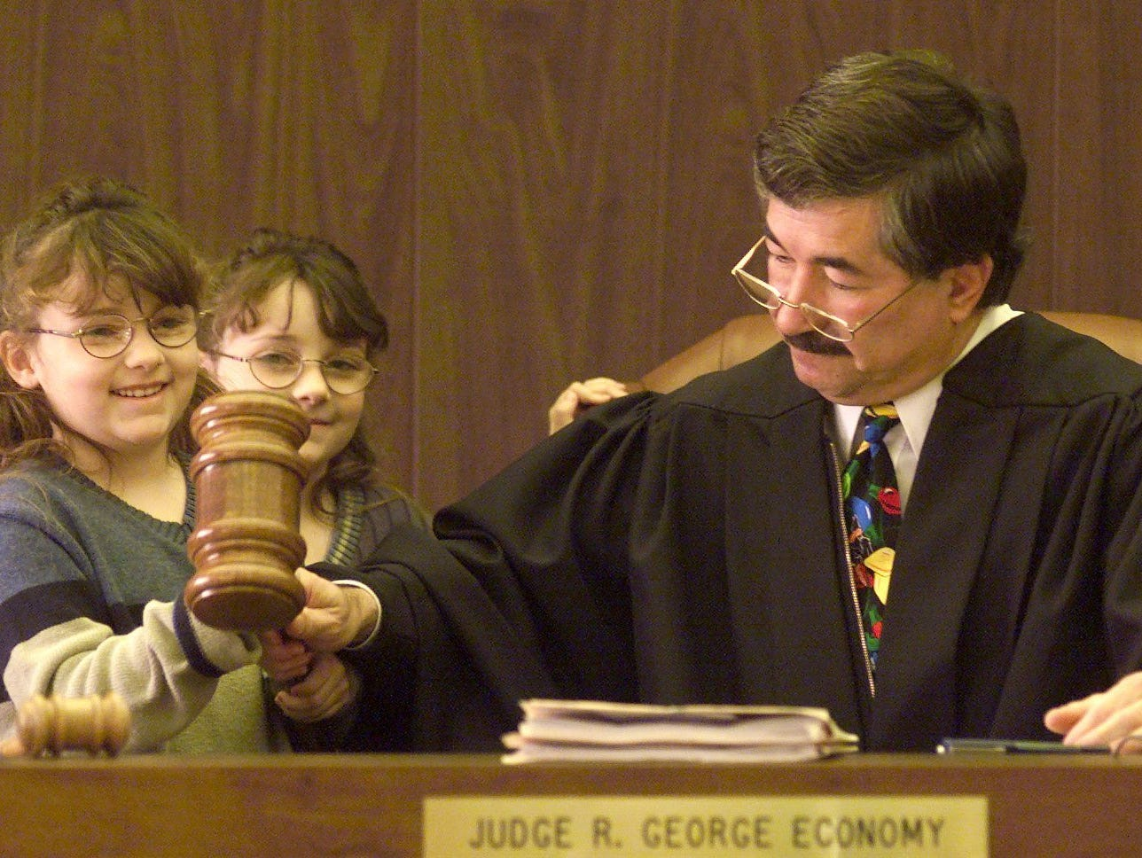 Judge George Economy gives Trisha Manko, 6, a hand with the over sized gavel to finalize the adoption of Trisha and her sister, Mariah, Dec. 23, 1999.