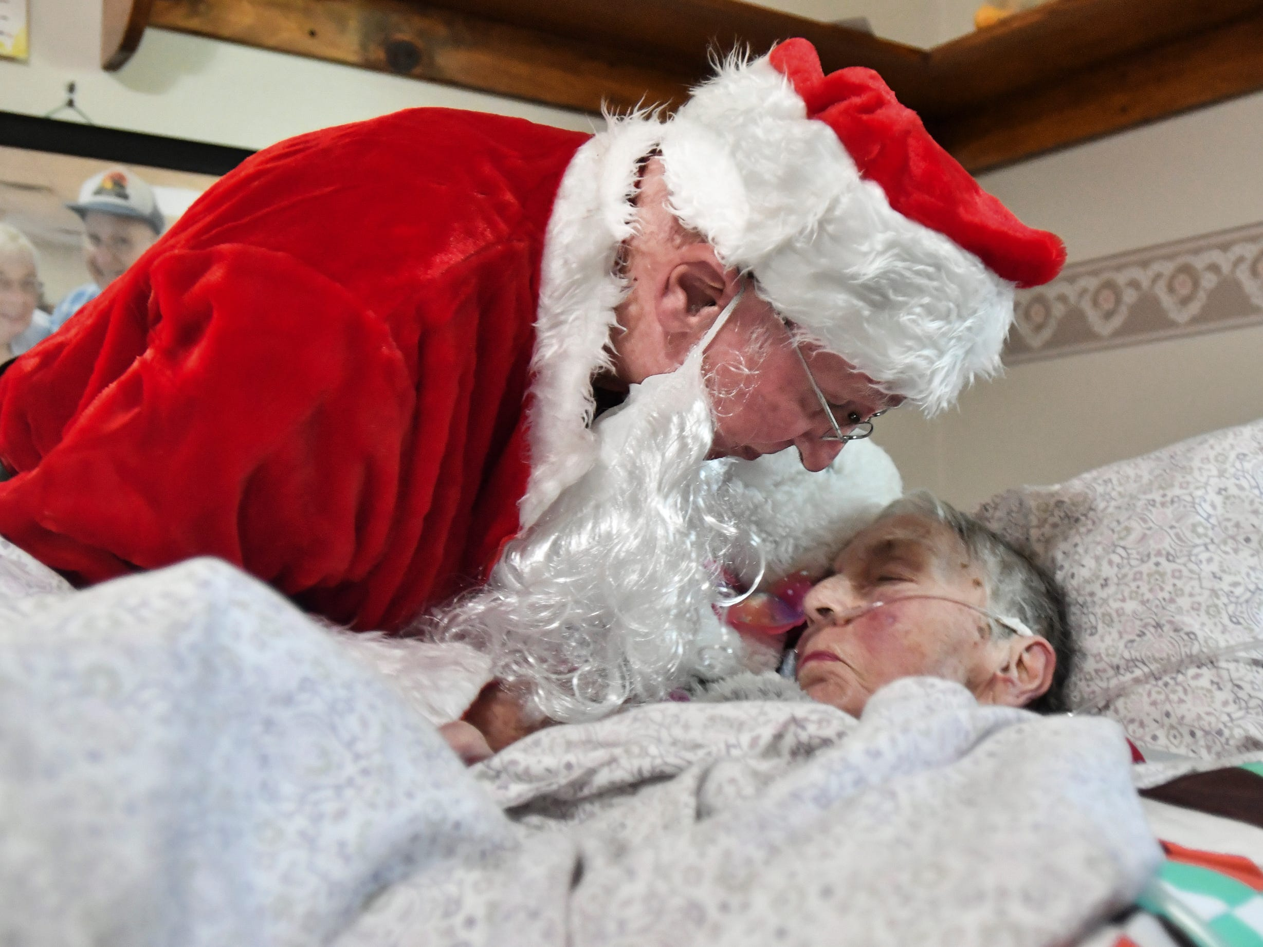 Don West, 90, of Eaton Rapids, leans in to kiss his wife Jackie goodnight, Saturday, Dec. 8, 2018, at Golden Days II Adult Foster Care in Charlotte following a Christmas party for residents and staff at the home.  Don hired a musician, brought gifts, and sang and danced for his wife of 64 years.  Jackie has been in a nursing home since her stroke in June of 2017.
