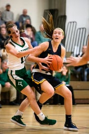 Pewamo-Westphalia junior Hannah Spitzley draws a foul going to the basket against St. Patrick freshman Irene Mackowiak during their Tuesday night game at Portland Middle School in Portland, Michigan.