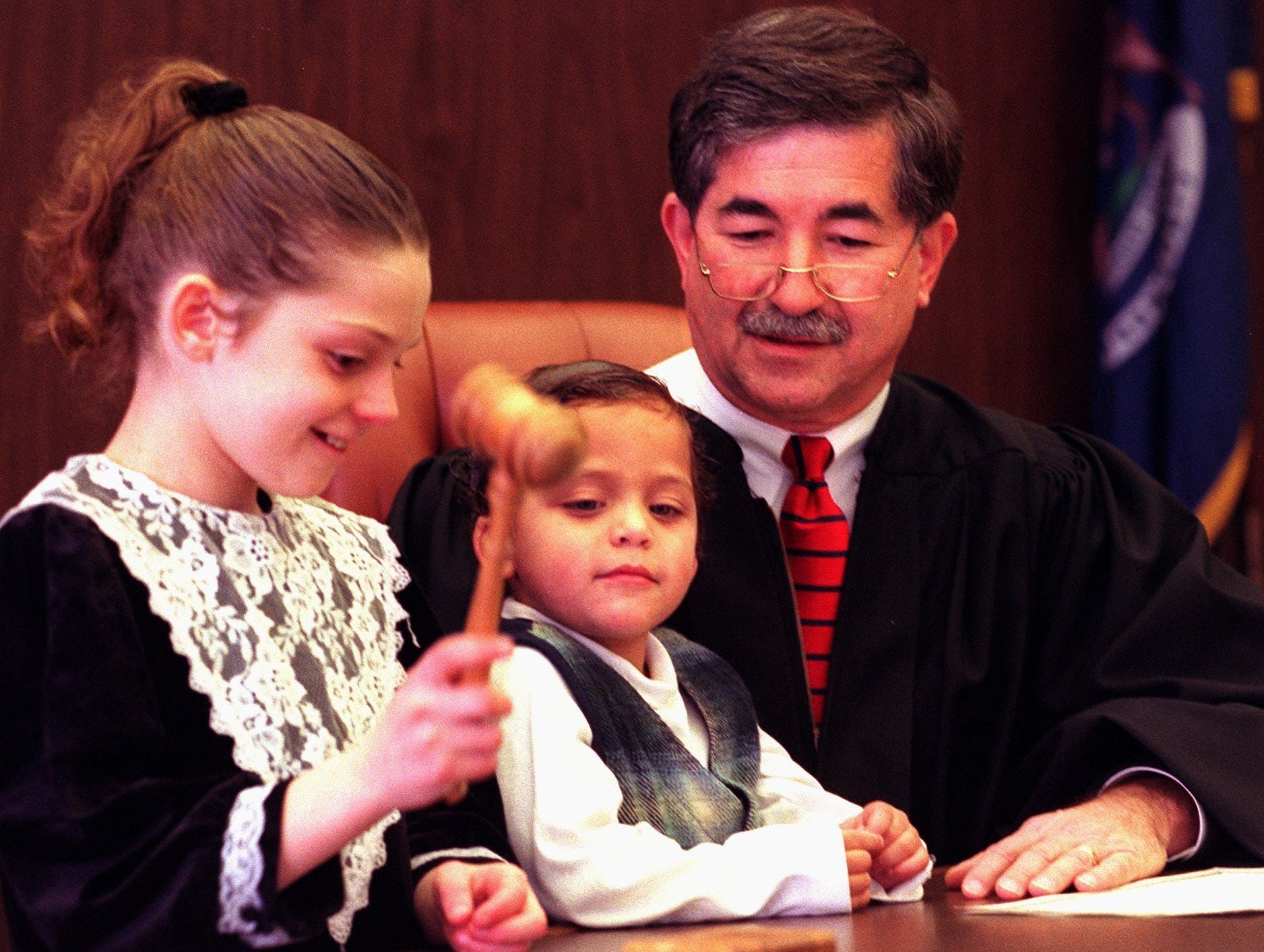 Ashley Keys, 10,  pounds the gavel to finalize adoption proceedings for herself and now official brother Marcus Keys, 3, center, in Judge George Economy's, right, courtroom Dec. 23, 1997. Ashley and Marcus were officially adopted by their mom Christina's husband Zettie Keys in the proceedings.