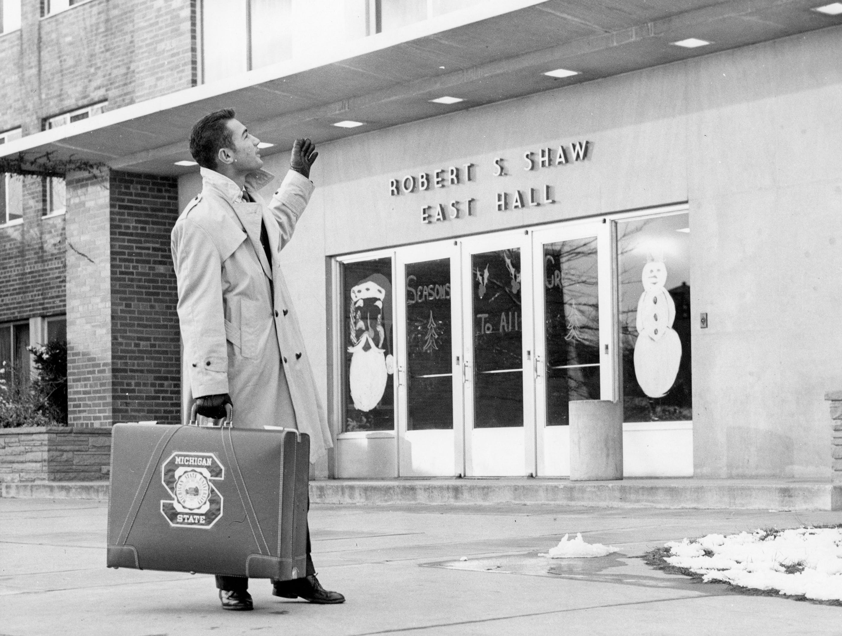 A male student, carrying a suitcase with a MSU sticker on it, waves outside to Shaw Hall. The windows of Shaw Hall are decorated for Christmas, date unknown.
