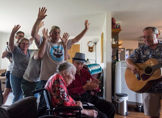 "Don West, middle, sings and claps along to the song ""You are my Sunshine,"" Tuesday, Aug. 21, 2018, at Golden Days II Adult Foster Care nursing home in Charlotte as friends and family dance behind them.  Jackie had a stroke in June of 2017 and has been in a nursing home since.  ""I know she's not coming home, so I figured I'd take the party to her,"" West said.  Also pictured is Dennis Michaels, right, a musician who's played several parties for the two.  Don and Jackie met Michaels at the community center in Eaton Rapids."