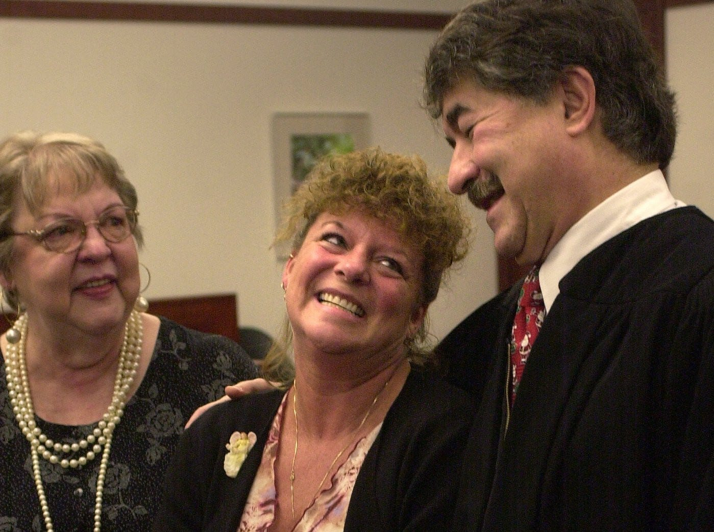 Susan Allen, center, beams after her parental adoption of Ty Anthany Adams Allen, 5, her grandson, center, was finalized in Probate Judge George Economy's courtroom Dec. 20, 2002. At left behind is Susan's mother and Ty's great grandmother Donna Compton, and at right is Judge George Economy.