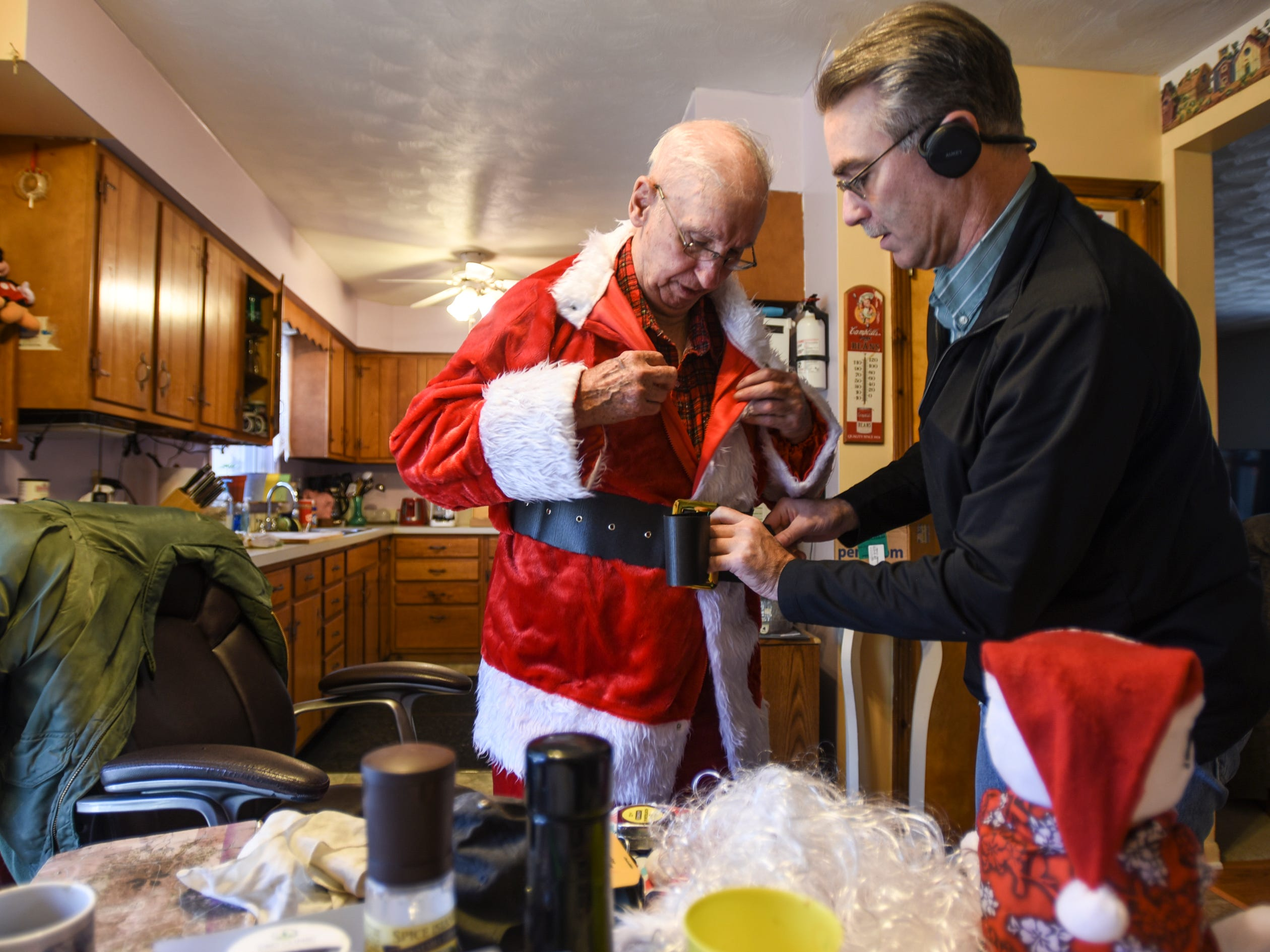 "Dana West, right, helps his 90-year-old father Don into his Santa suit Saturday, Dec. 8, 2018, at their home in Eaton Rapids.  Don is preparing to go to a Charlotte adult foster care home to visit Jackie, his wife of 64 years.  She had a stroke in June of 2017.  Jackie is fed through a tube, and can only move her right hand.  ""She'll never come back home,"" he says, ""unfortunately she's not getting any better, so I'm gonna take the party to her.""  Don has visited her every day since the stroke."